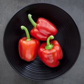 Red Capsicum on Black Plate. — Stock Photo