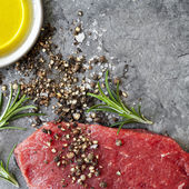 Raw Beef Steak with Peppercorns Sea Salt Olive Oil and Rosemary — Stock Photo