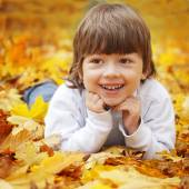 Happy boy in leaves of autumn lies — Stock Photo