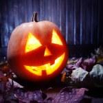 Jack o lanterns Halloween pumpkin face on wooden background — Stock Photo #54594355