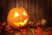 Jack o lanterns  Halloween pumpkin face on wooden background — Stock Photo