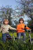 Two brothers ride bikes — Stock Photo