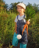 Boy with a carrot and a watering can — Stock Photo