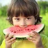 Glückliches Kind essen Wassermelone im Garten — Stockfoto