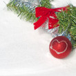 Bright red Christmas ball ornament in snow with a wreath and tinsel — Stock Photo #64325185