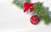 Bright red Christmas ball ornament in snow with a wreath and tinsel — Stock Photo