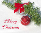 Bright red Christmas ball ornament in snow with a wreath and tinsel, with text Merry Christmas — Stock Photo