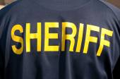 Closeup image of a back of a sheriff's deputy, with text sheriff in yelllow letters — Stock Photo