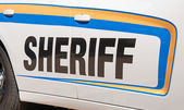 Sheriff text in black on side of a white patrol car lined with yellow and blue decal stripes — Stockfoto
