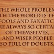 The whole problem with the world is that fools and fanatics are always so certain of themselves, and wiser people so full of doubts - quote on wooden red oak background — Stock Photo #71279677