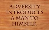 Adversity introduces a man to himself - quote by unknown author on wooden red oak background — Stock Photo