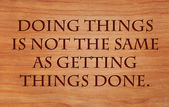 Doing things is not the same as getting things done - quote on wooden red oak background — Stock Photo