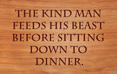 The kind man feeds his beast before sitting down to dinner - Hebrew Proverb on wooden red oak background — Stock Photo