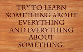 Try to learn something about everything and everything about something - quote on wooden red oak background — Stock Photo