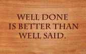 Well done is better than well said - motivational quote on wooden red oak background — Stock Photo