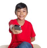 Jeune fille asiatique avec la télécommande de télévision — Photo