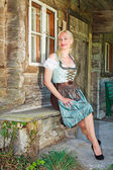 Bavarian blonde woman sitting elegantly in a dirndl — Stock Photo