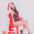 Young sexy Santa woman sitting in front of Christmas gifts in socks and sexy lingerie, attractive brunette with big cleavage — Stock Photo #52587331