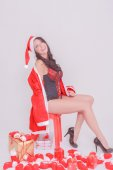 Young sexy Santa woman sitting in front of Christmas gifts in socks and sexy lingerie, attractive brunette with big cleavage — Stok fotoğraf