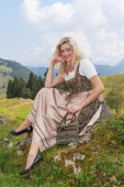 Young woman in dirndl, sitting in nature on a rock — Stock Photo