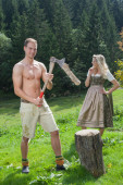 Scene of a Bavarian couple in traditional costumes chopping wood — Stock Photo