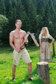 Bavarian couple in love chopping wood in fashionable dress clothing — Stock Photo