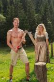 Bavarian couple in the work of firewood — Stock Photo