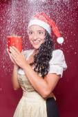 Christmas woman in dirndl with packet during snowfall — Stock Photo
