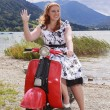 Young curvy woman sitting on a scooter with a petticoat dress and waving — Stock Photo #54290049