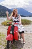Young curvy woman sitting on a scooter with a petticoat dress and waving — Stock Photo