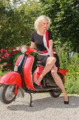 Woman posing in fashionable summer dress on a scooter — Stock Photo