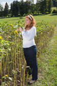 Beautiful red-haired overweight woman on a sunflower field. — Stock Photo