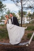 Young married couple is frivolous on a large swing. — Stock Photo