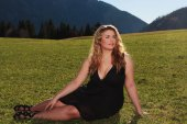 Elegant woman with oversized half lying on a meadow in the Alps — Stock Photo