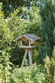 Three-legged wooden bird table — Stock Photo