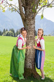 Two smiling women in dirndl hold on to a tree. — Stock Photo