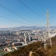 Power transmission line pole and wires on a hill over a city — Stock Photo #62939413