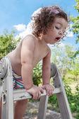 Baby girl standing on ladder — Stock Photo