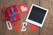 Instant photo with gift and hearts — Stock Photo