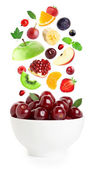 Falling fresh fruits and berries in bowl — Stock Photo
