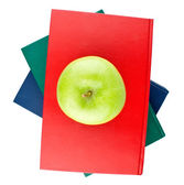 Three color books and green apple view from top — Stock Photo