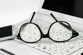 Eyeglasses  and cell phone on a small laptop — Stock Photo