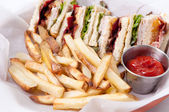 Clubhouse sandwich with fries — Stock Photo