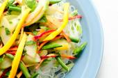 Fresh vegetable stir fry with sliced mango over glass noodles — Stock Photo