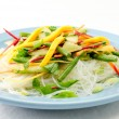 Fresh vegetable stir fry with sliced mango over glass noodles — Stock Photo #57790627