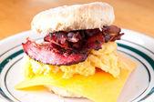 Hearty egg, cristpy bacon, cheese sandwich on a homemade butterm — Stock Photo