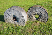 Ancient millstone on the grass, natural background — Stock Photo