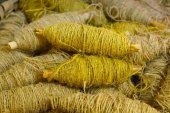 Old bobbin with yellow jute rope — Stock Photo