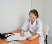 The doctor the therapist fills in the working magazine, sitting  — Stock Photo