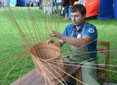 The handicraftsman spins a basket from a rod at fair of national — Foto de Stock